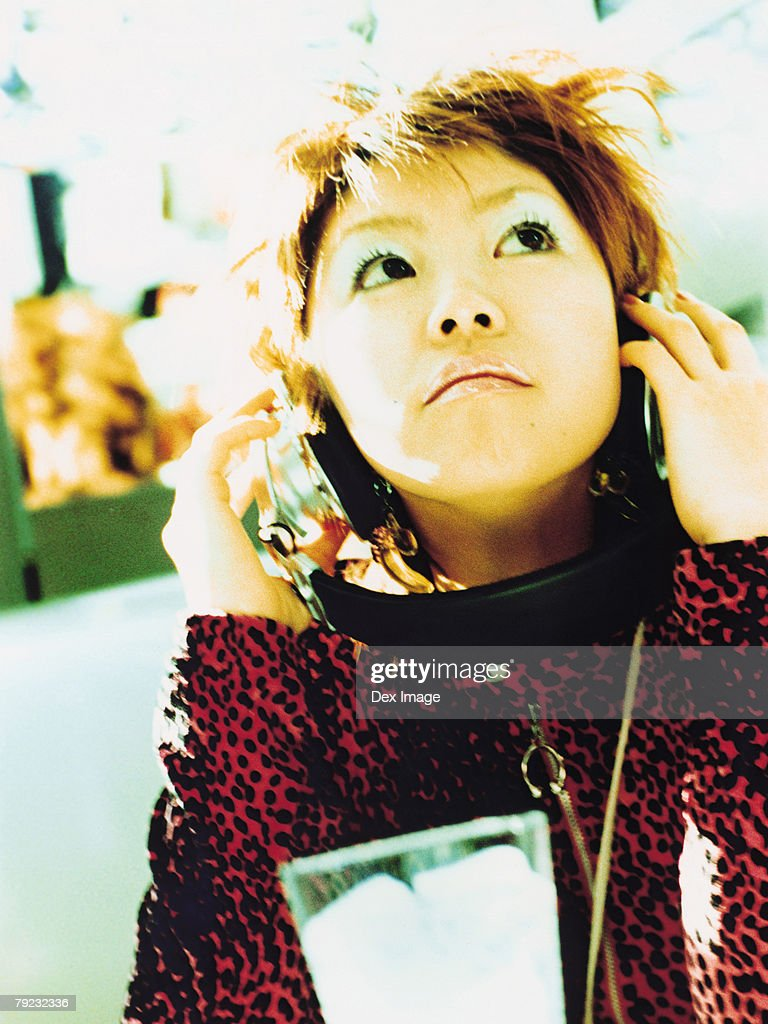 Young woman listening to headphones, portrait, close up : Stock Photo