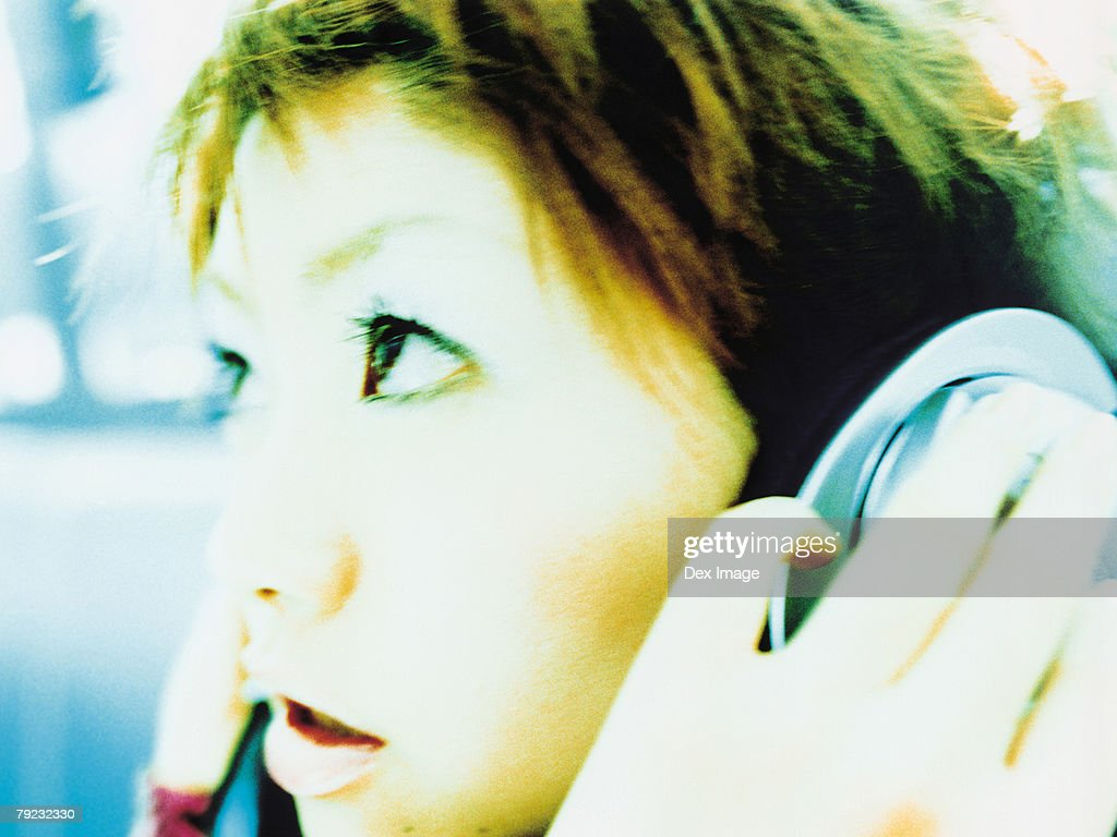 Young woman listening to headphones, profile, close up : Stock Photo