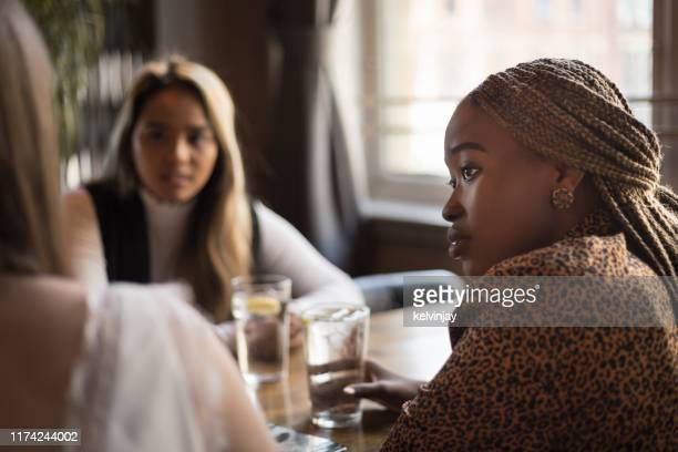young woman listening to her friends in a cafe bar - friendship stock pictures, royalty-free photos & images