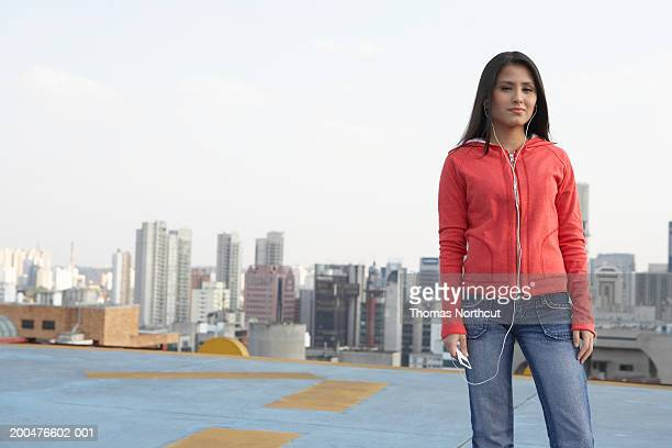 Young woman listening to MP3 player on rooftop, portrait