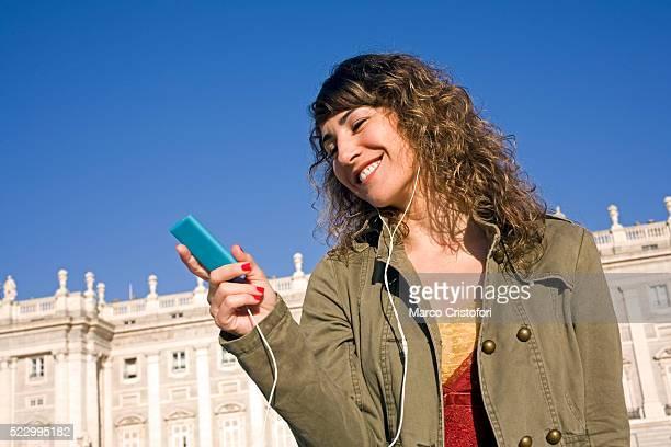 young woman listening to mp3 player - marco cristofori fotografías e imágenes de stock