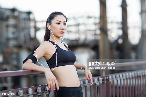Young woman listening to music after exercising outdoors