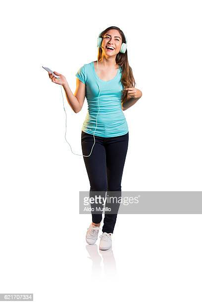 Young woman listening to music and laughing
