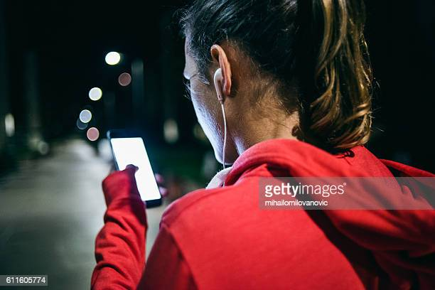 Young woman listening to music at night