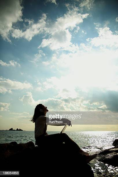 young woman listening to music near the sea