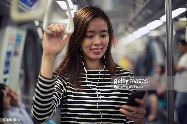 Young woman listening to music on a train.