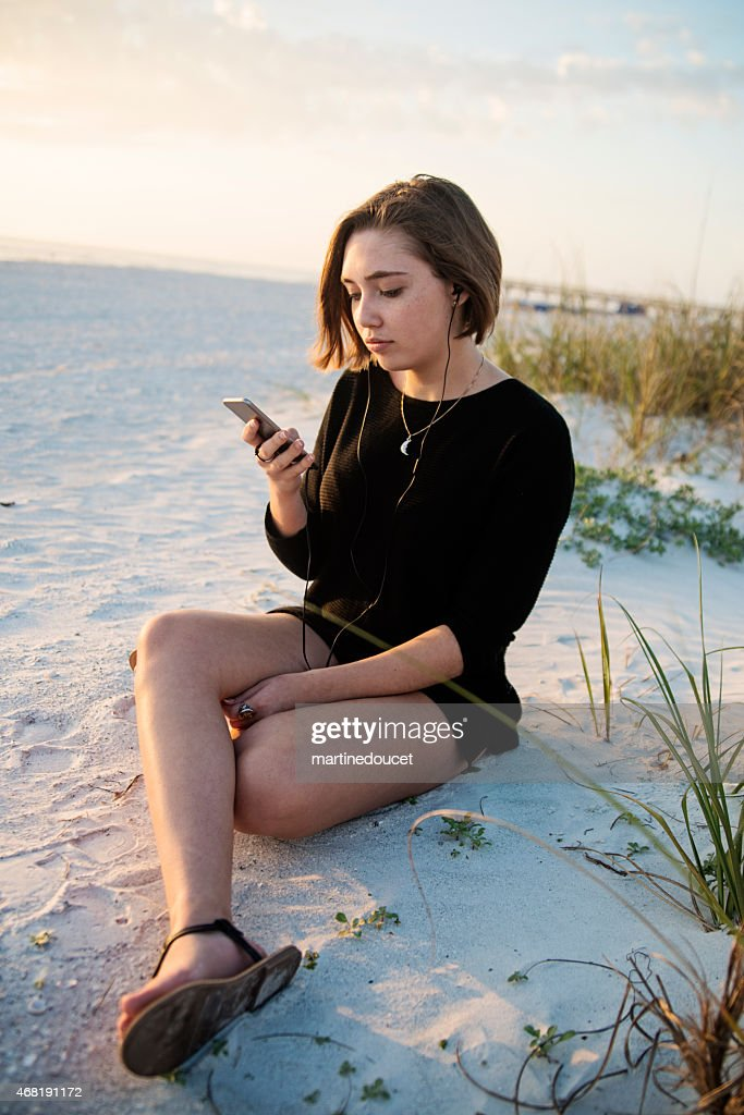 Young woman listening to music on beach at sunset. : Stock Photo