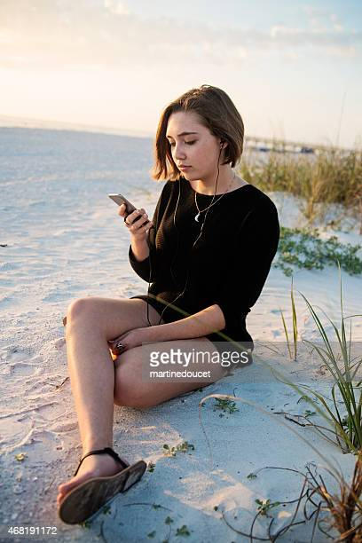 "young woman listening to music on beach at sunset. - ""martine doucet"" or martinedoucet stockfoto's en -beelden"