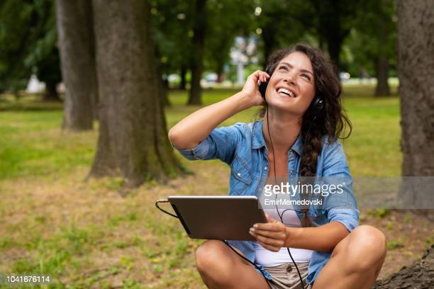 young woman listening to music on digital tablet outdoors - emir memedovski stock pictures, royalty-free photos & images