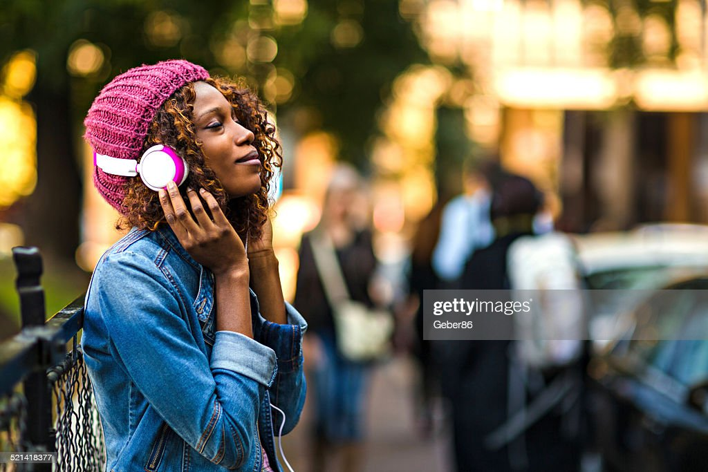 Young woman listening to music on mobile phone : Stock Photo