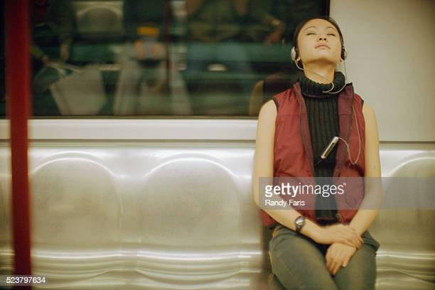 Young Woman Listening to Music on Subway