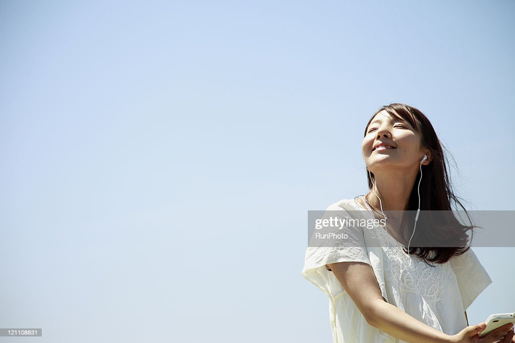Young woman listening to music outside : ストックフォト
