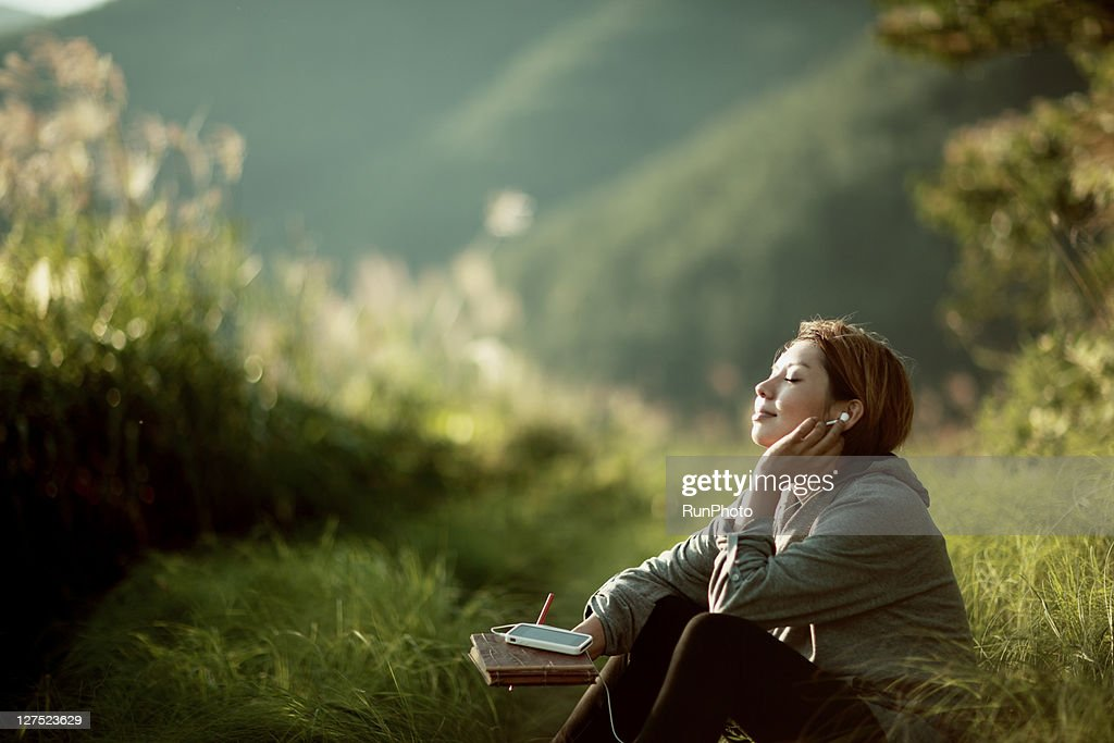 young woman listening to music outside : Stock Photo