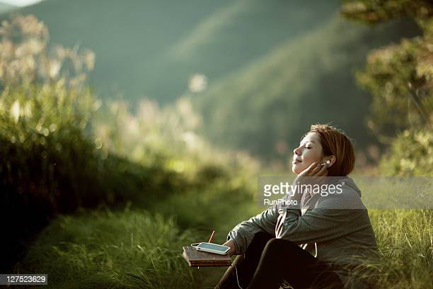 young woman listening to music outside