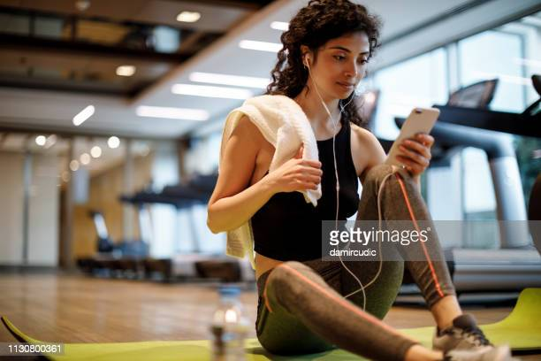 young woman listening to music over cell phone at the gym - sports training stock pictures, royalty-free photos & images