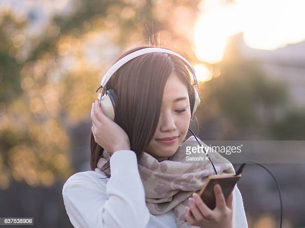young woman listening to music over headphones at park - yokohama stock pictures, royalty-free photos & images