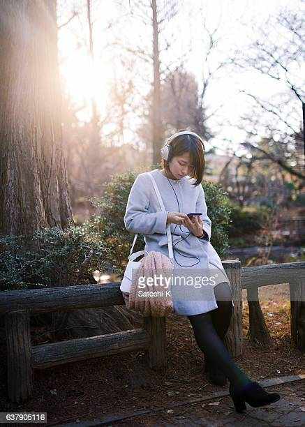Young woman listening to music over headphones
