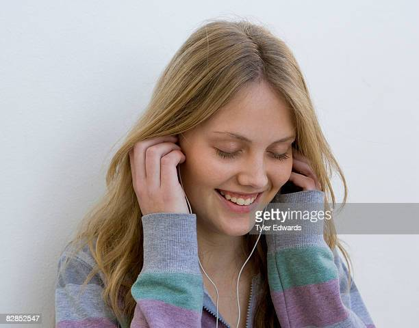 Young woman listening to music using earphones