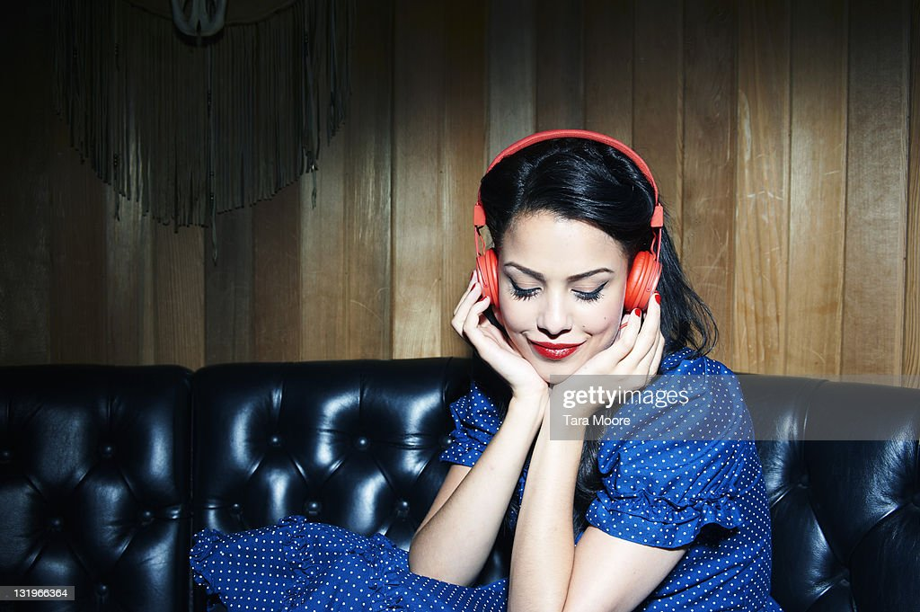 young woman listening to music wearing headphones : Stock-Foto