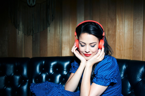 young woman listening to music wearing headphones - gettyimageskorea