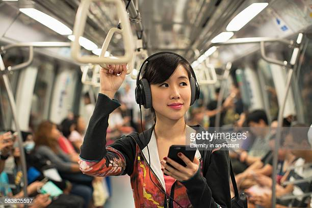 young woman listening to music while commuting - chinese music stock pictures, royalty-free photos & images