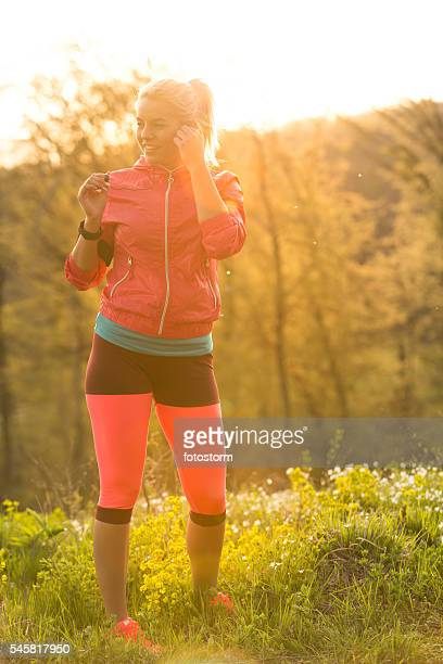 Young woman listening to music while exercising in nature