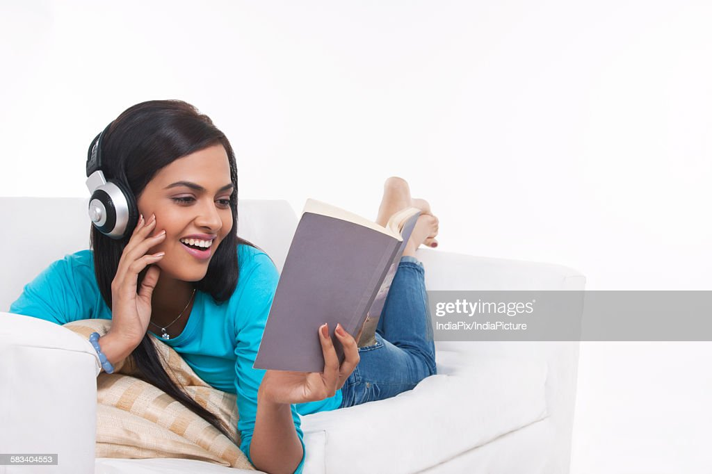 Young woman listening to music while reading : Stock Photo