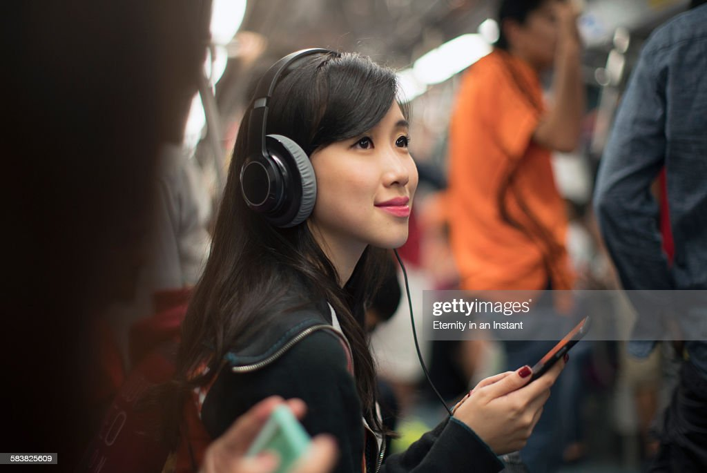 Young woman listening to music while travelling : Stock Photo