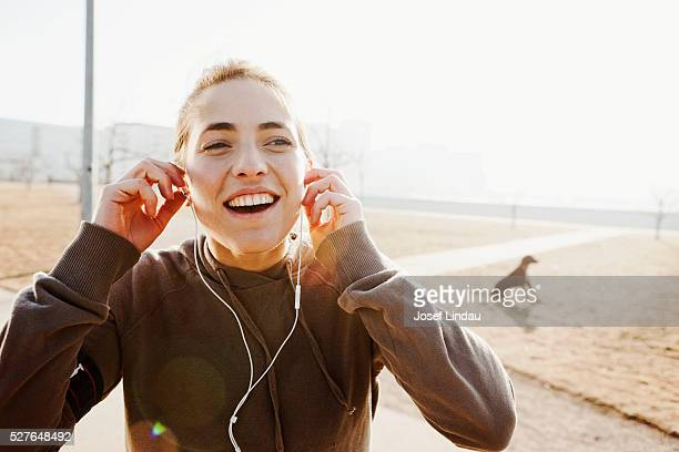 young woman listening to music with dog in background - joggeuse photos et images de collection