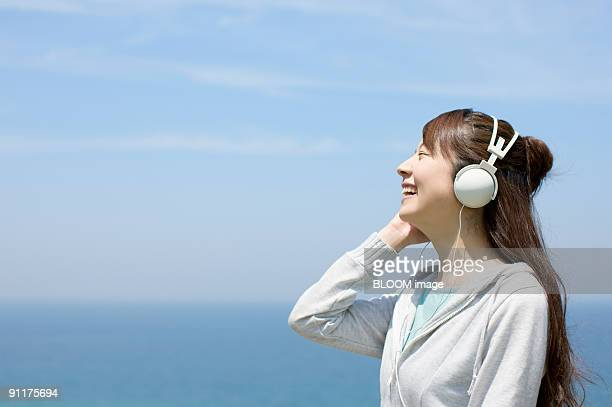 Young woman listening to music with headphones by the sea