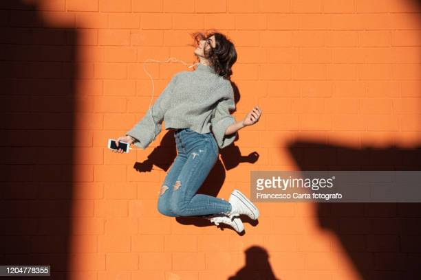 young woman listening to the music and jumping - jumping stock pictures, royalty-free photos & images