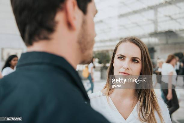 young woman listening to young men outdoors - stranger stock pictures, royalty-free photos & images