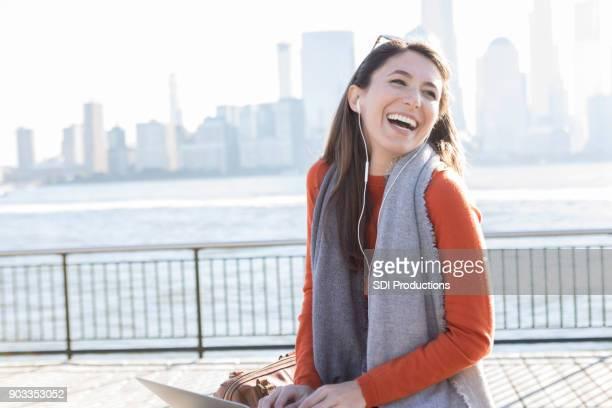 若い女性は、桟橋で音楽を聴いてください。