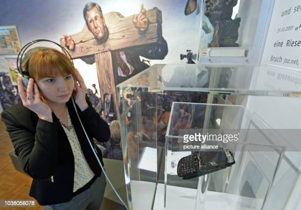 A young woman listens to the message thenPresident Wulff left on the answering machine of Bild editorinchief Diekmann in 2012 at a special exhibition...
