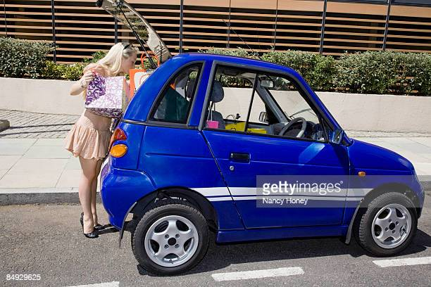 Young woman loading electric car