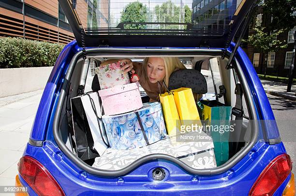 young woman loading electric car - nancy green stock pictures, royalty-free photos & images
