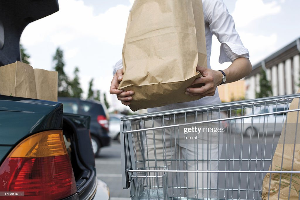 A young woman loads her groceries into her car : Stock Photo