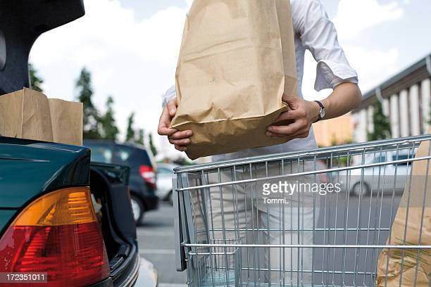 a young woman loads her groceries into her car - full stock pictures, royalty-free photos & images