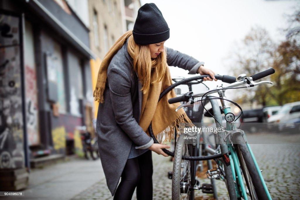 Jonge vrouw vergrendeling fiets in de stad tijdens de winter : Stockfoto