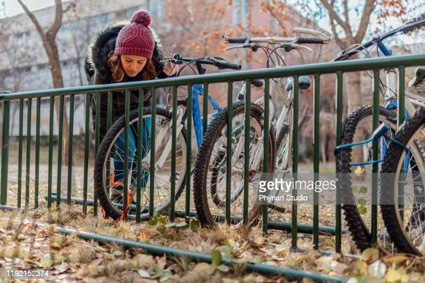 young woman locking bicycle in university during winter - lock sporting position stock pictures, royalty-free photos & images