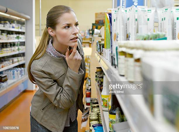 young woman loking at grocery in supermarket