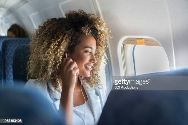 a young woman look out a plane window smiles - aeroplane stock pictures, royalty-free photos & images