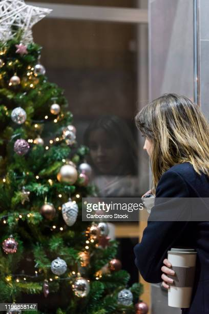 young woman looking a window shop at night - snood headwear stock photos and pictures