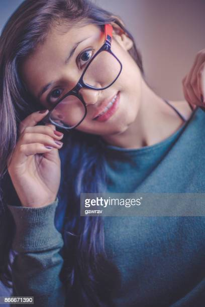 Young woman looking above the eyeglasses.
