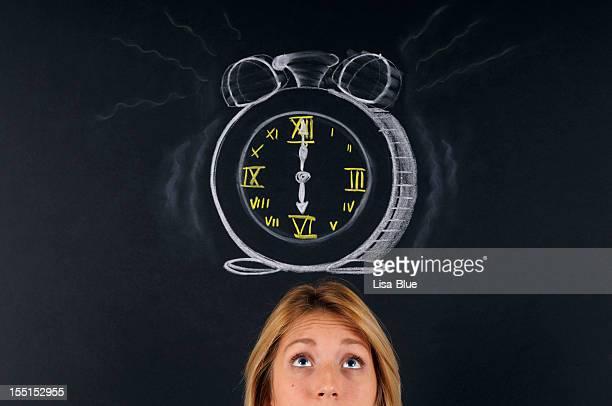 ている若い女性の目覚まし時計