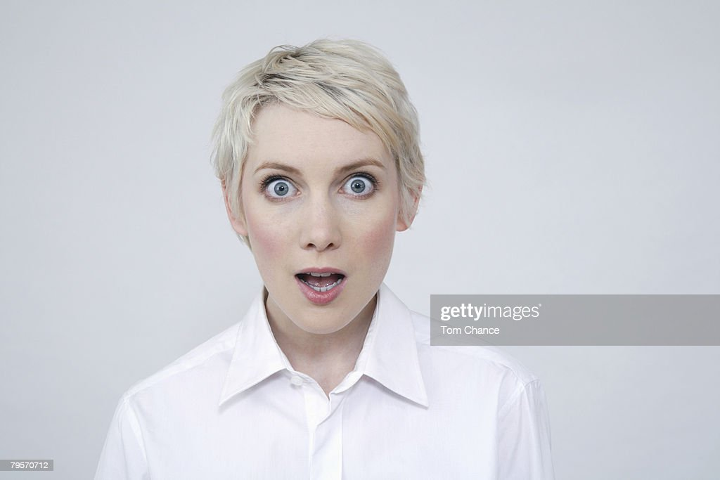 Young woman looking amazed, portrait : Stock Photo