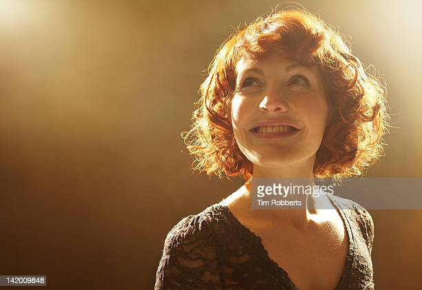 young woman looking around and smiling. - glowing stock pictures, royalty-free photos & images