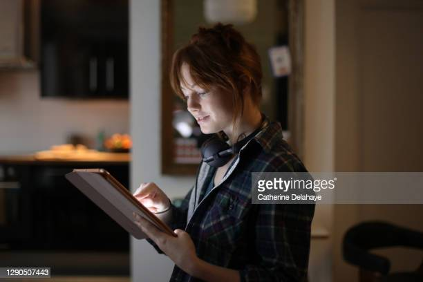 a young woman looking at a digital tablet at home - france stock pictures, royalty-free photos & images