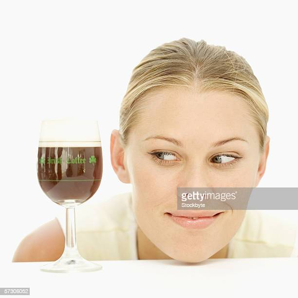 Young woman looking at a glass of Irish coffee