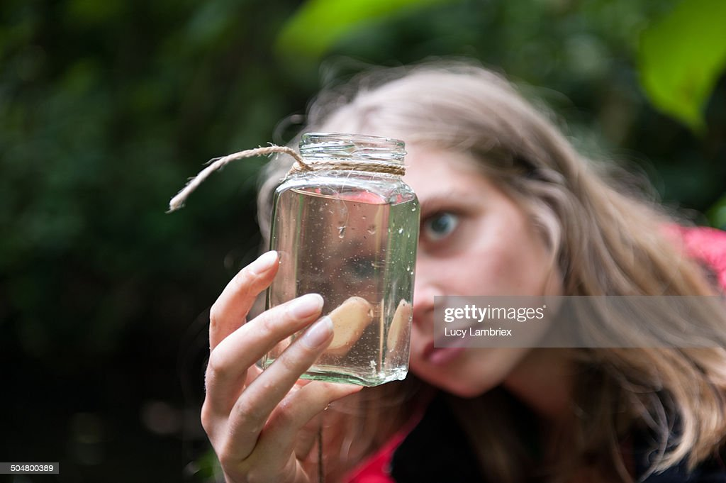 Young woman looking at a jar of ditchwater : Stockfoto